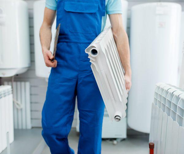Plumber holds heating radiator, plumbering store